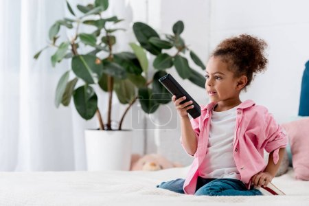 Adorable African american child sitting on the bed and and switching channels on tv