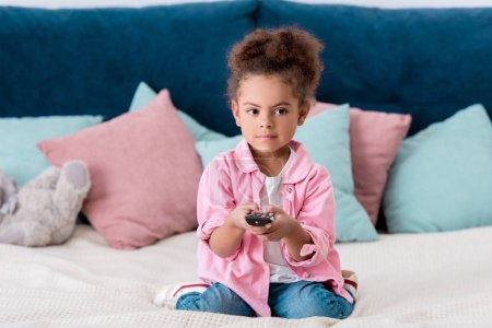 Cute  African american child sitting on the bed and and switching channels
