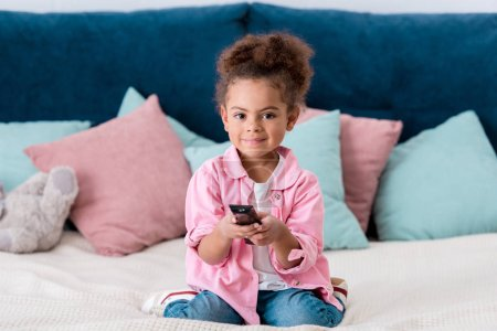 Curly  African american child sitting on the bed and press the buttons on remote