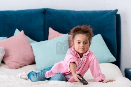 Cute African american kid sitting on the bed with tv remote
