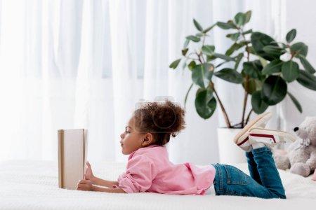 Photo pour Adorable enfant afro-américain allongé sur le lit et lisant un livre - image libre de droit