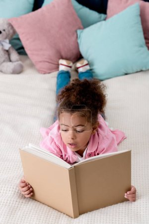Surprised  African american kid laying on the bed and reading book