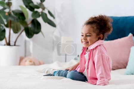 Photo for Smiling adorable African american child sitting on the bed - Royalty Free Image