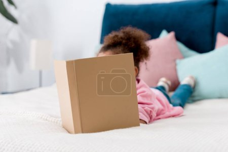 Curly African american child laying on bed and reading book