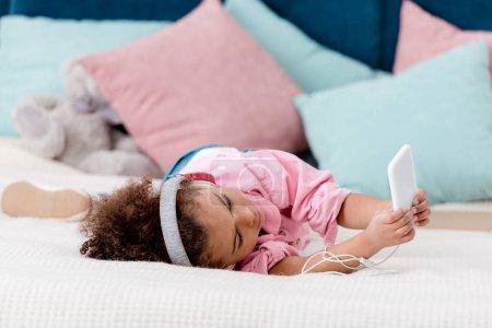 Photo pour Adorable enfant afro-américain allongé sur le lit et l'écoute de la musique sur son smartphone dans les écouteurs - image libre de droit