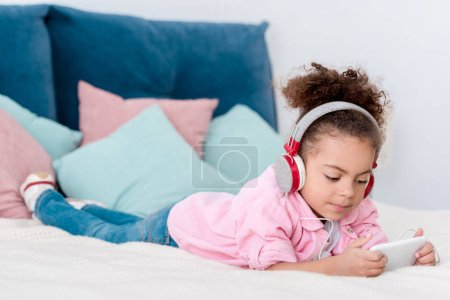 cute african american kid lying on the bed and listening music in headphones