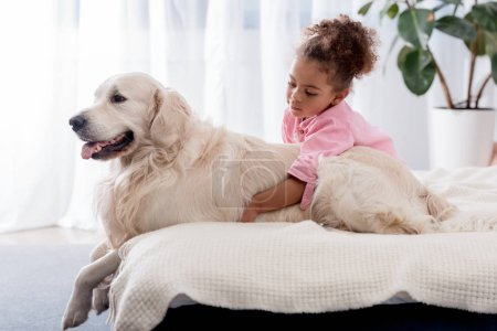 Cute african american kid hugs her retriever on the bed