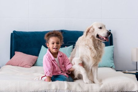 Smiling african american child sitting on the bed and holding dog paw