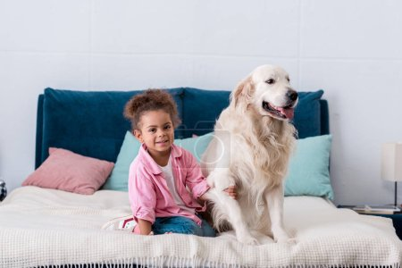 cute african american kid sitting on the bed and holds dog paw