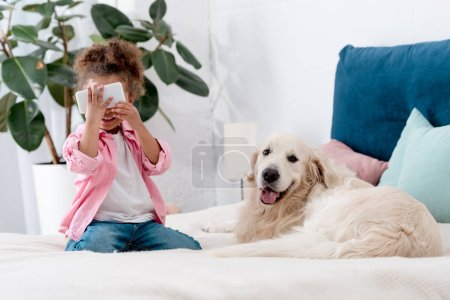 cute african american child sitting on the bed with retriever and holding smartphone near face