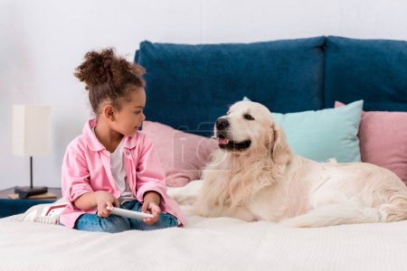 cute african american child sitting on the bed with golden retriever and playing with smartphone
