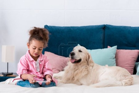 Curly african american kid sitting on the bed with retriever and looking in smartphone