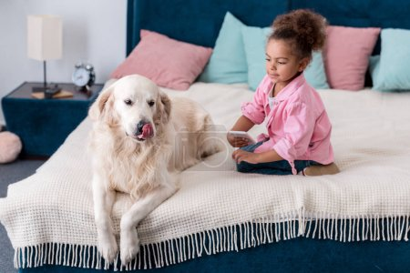 Cute african american kid sitting on the bed with smartphone and golden retriever