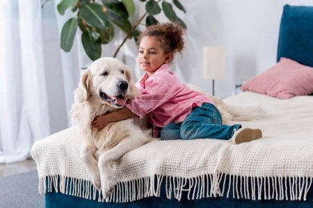 Cute african american kid sitting on the bed and  hugging her dog
