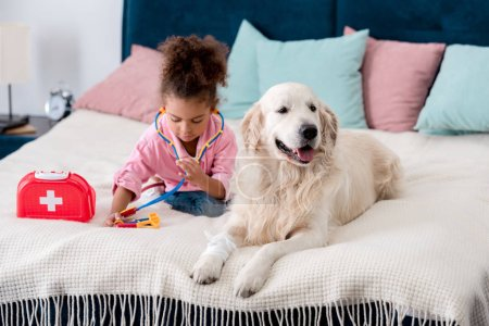 Adorable african american kid sitting on the bed with toys and retriever