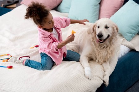Cute african american kid playing doctor with her dog