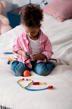 Curly african american kid playing with toy stethoscope on the bed