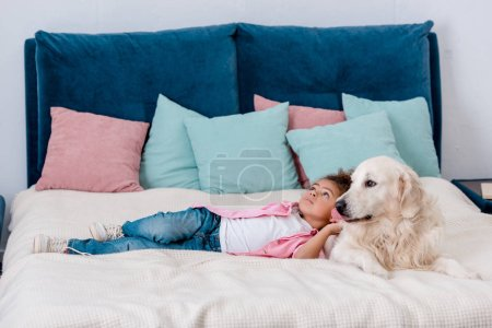 Adorable little african american kid in pink jacket lying on bed with dog while looking away
