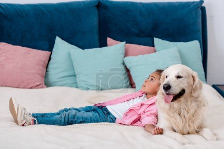 Adorable little african american kid in pink jacket lying on bed and leaning to dog