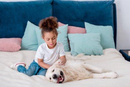 Photo pour Adorable petit enfant africain-américain caresser heureux chien assis sur le lit - image libre de droit