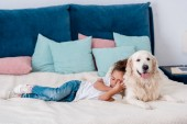 Cute little african american kid lying on bed and leaning to dog