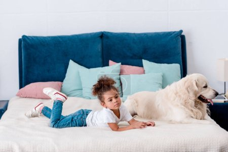 Cute little african american kid with happy dog lying on bed