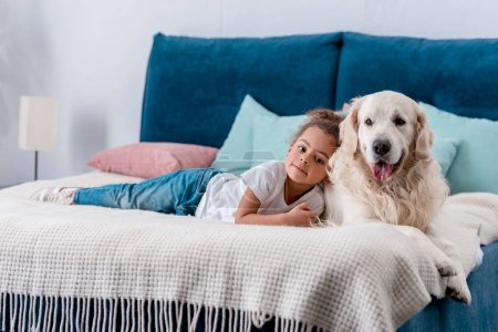 Cute little african american kid with happy dog lying on bed with colourful pillows