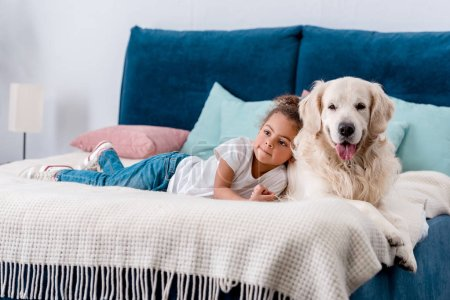 Adorable little african american kid with happy dog looking away while lying on bed