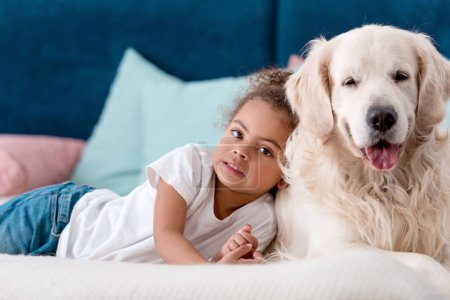 Adorable little african american kid with happy dog lying on bed