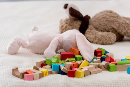 Colourful toy cubes and teddy bears lying on plaid