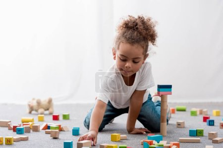 Adorable african american child in white t-shirt playing with colourful toy cubes
