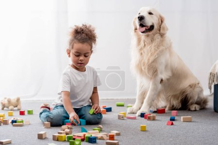 Cute african american child playing with colourful toy cubes and happy dog