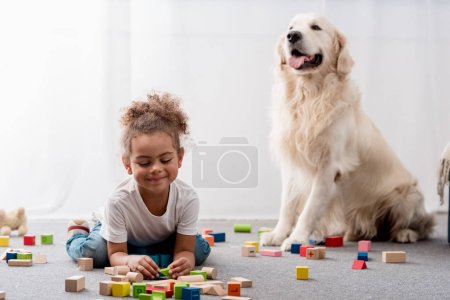 Adorable african american child playing with toy cubes and dog