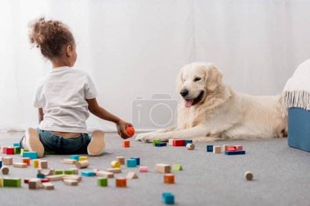 little kid in white t-shirts with happy dog playing with toy cubes