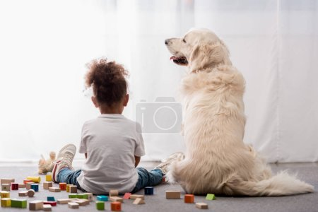 Back view of little kid in white t-shirts with happy dog surrounded by toy cubes