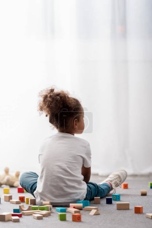 Back view of little child in white t-shirts surrounded by colourful toy cubes