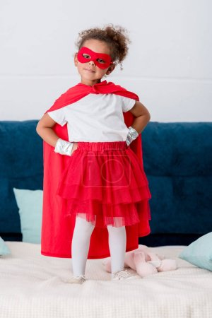 Cute little african american kid in red superhero costume with hands on hips standing on bed