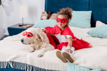 Cute little african american kid with dog in red superhero costumes sitting on bed