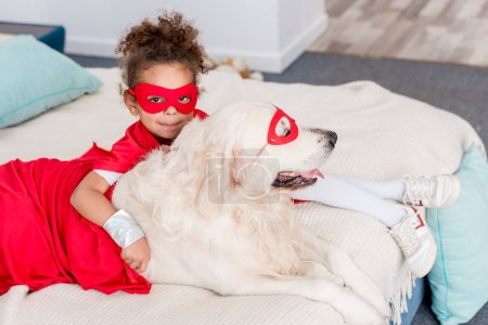 Cute little african american kid with dog in red superhero costumes lying on bed