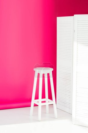 white painted room divider and chair with bright pink wallpaper at background