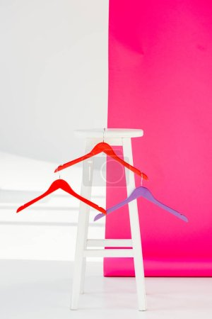 multicolored painted hangers with white wooden chair