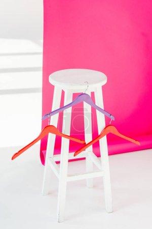 Photo pour Cintres peints multicolores avec chaise en bois blanc et rose wallaper - image libre de droit