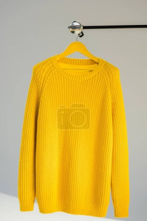 knitted yellow sweater on hanger at grey background