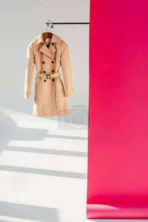 Photo for Elegant beige trench coat on hanger with pink wallpaper - Royalty Free Image