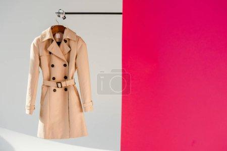 Photo pour Élégant Trench-Coat beige sur cintre à fond rose et gris - image libre de droit
