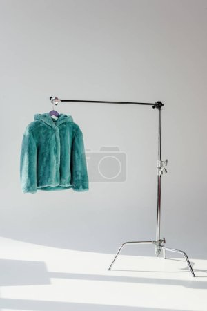 fluffy green faux fur coat hanging on rack at grey background