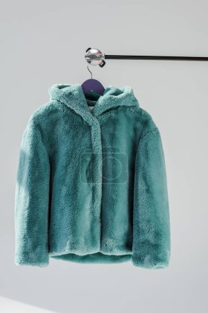 close up of fluffy green faux fur coat hanging on rack at grey background