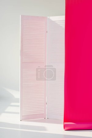 white room divider with bright pink rolled out wallpaper