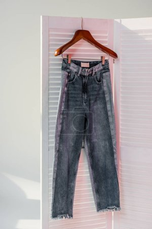 close up of jeans hanging on white room divider with sunbeams