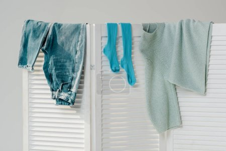 Photo for Close up of blue clothes hanging on white room divider isolated on grey - Royalty Free Image